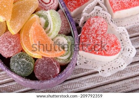 Present box with sweets on wooden background