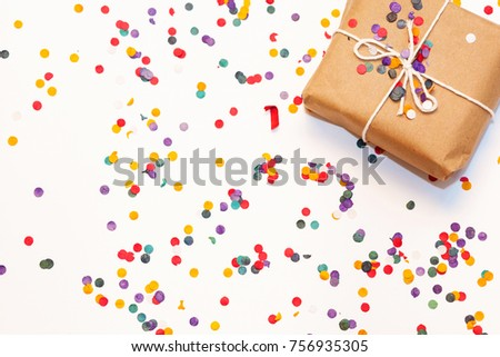 Present box with white bow on white background with multicolored confetti. Flat lay style. Christmas and new year concept