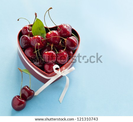 Present for Valentine's day. Red heart shaped box with sweet cherries and white ribbon on light blue background.