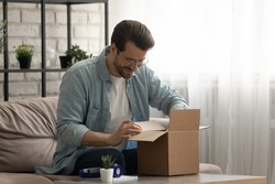 Present from distant friend. Happy millennial man unpack open box with birthday gift surprise received by mail. Smiling young guy has pleasure to receive package with consumer goods purchased online