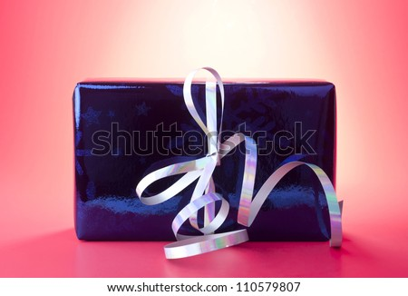 Present or gift wrapped in blue shiny wrapping paper with silver curly ribbon against red background.