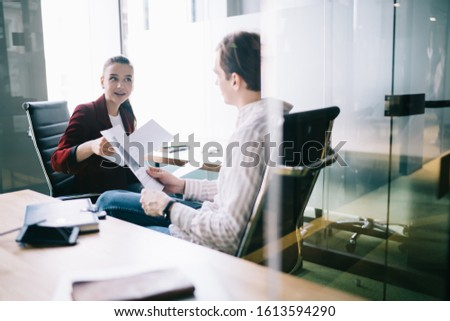 Presentable entrepreneur sitting with documents in hand in bright office and discussing with female business partner details of common project