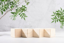 Presentation and display product - wooden cube podiums in row with green branch of tree in sunlight on white wood board and grey marble wall.
