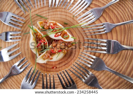 Presentation first plate of pasta shells with meat sauce and tomato