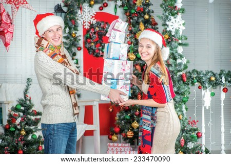 Presentation of gifts. Loving guy gives gifts to his girlfriend for Christmas. Young couple in love man and pretty girl wearing sweater and scarf at home