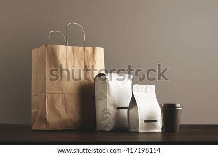 Presentation of retailer package set: craft paper bag, big pouch, small container and take away glass with cap. Filled with goods, blank labeled, merchandise pack #417198154