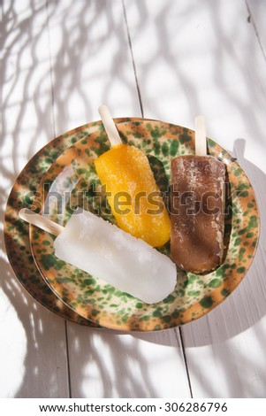 Presentation of three icicles summer fruit on colorful plate