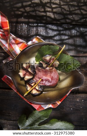 Presentation on plate skewer with figs and ham