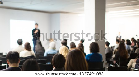 Presenter at Conference Meeting Event Photo. Speaker on Stage at Business Seminar. Audience Watching a Manager Presentation. Blurred Image of Lecturer Presenting To Audience During Speech.