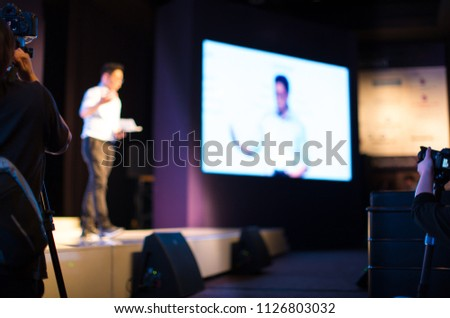 Presenter Presenting on Stage at Conference Hall Meeting. Professional Lecture. Blurred De-focused Unidentifiable Presenter. Corporate Executive Manager. Speaker Teacher. Crowd. Camera Man Crew.