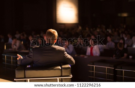 Presenter Presenting on Stage at Conference Meeting. Professional Lecture. Blurred De-focused Unidentifiable Presenter and Audience. Corporate Executive Manager Speaker. People Attendees