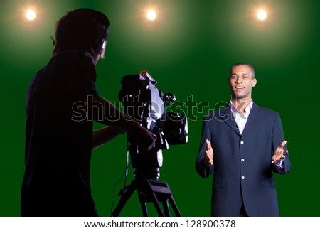 Presenter talking to camera in a green screen studio with silhouetted cameraman in foreground and studio lights in the background. #128900378