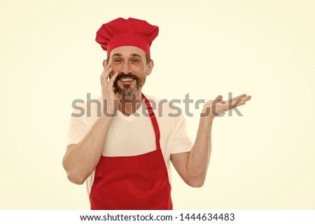 Presenting product. Bearded mature man in chef hat and apron pointing hand aside. Senior cook with beard and moustache wearing bib apron. Mature chief cook in red cooking apron, copy space. #1444634483