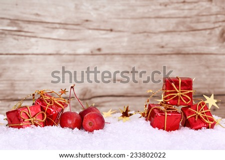 Presents and apples in the snow, space for text