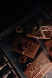 Presents and gifts beautifully wrapped in beige ecological paper, decorated with natural materials: dry flowers, skeleton leaves, lace and twine on table in dark room, rustic, romantic provence style.