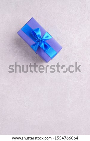 Presents background for festive season, copy space. Gift box on stone background. Reward, gift for holiday or birthday, festivity or greeting concept
