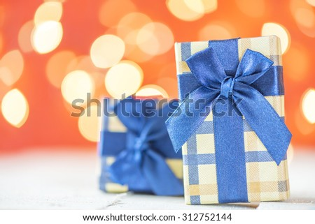 Presents with blue ribbons. Small presents with blue ribbons on red sparkle blurred background.