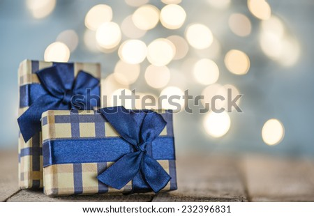 Presents with blue ribbons. Small presents with blue ribbons on sparkle blurred background.