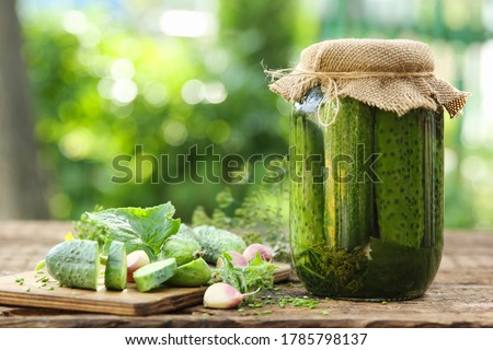 Preservations, conservation. Salted, pickled cucumbers in a jar on an old wooden table in the garden. Summer, sunny day. Cucumbers, herbs, dill, garlic. Rustic. Background image, copy space,horizontal Сток-фото ©