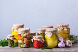 Preserved and fermented food. Assortment of homemade jars with variety of pickled and marinated vegetables on a wooden table. Housekeeping, home economics, harvest preservation