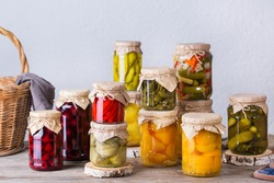 Preserved and fermented food. Assortment of homemade jars with variety of pickled and marinated vegetables, fruit compote on a wooden table. Housekeeping, home economics, harvest preservation