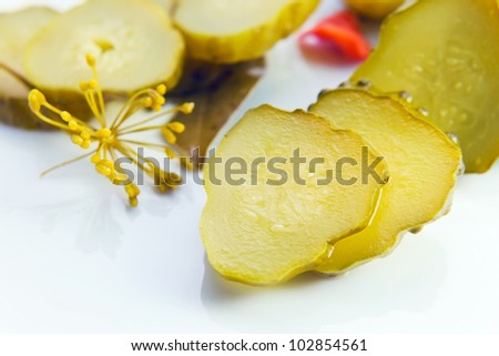 preserved  cucumbers on a white plate . Macro shot , focus on a center.