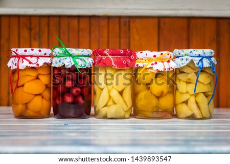 Preserved food in jar, fruit compote on wooden table. Variety of homemade preserved fruit in kitchen. Apricot, cherry, pear, plum and apple compotes