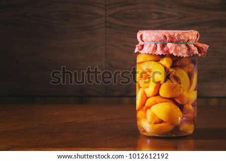 Preserved fruit in jar, compote of peaches. Homemade conserved fruits in glass on a wooden table. Vegetarian organic food.  #1012612192