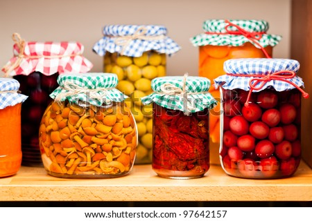 Preserved fruits and vegetables on the wooden shelf. Shallow deep of focus.