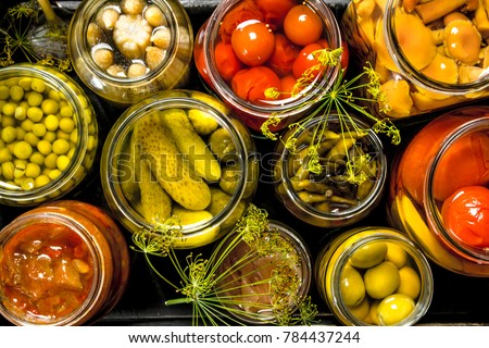 Preserves vegetables in glass jars in an old box. On the black chalkboard.
