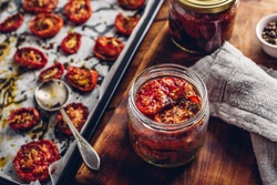Preserving in Olive Oil of Sun Dried Tomatoes with Herbs in a Glass Jar