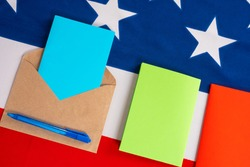 Presidential election via USA Postal Service. Multicolored sheets paper on USA flag. Envelope and pen as symbol election through mail in US. Concept - different colors represent different candidates