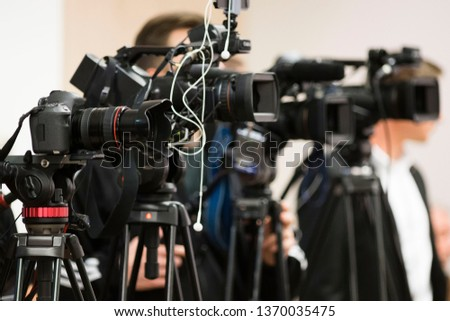 press and media photographer on duty in public news coverage event for reporter and mass communication #1370035475