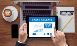 Press Release  concept on the tablet pc screen held by businessman hands, top view