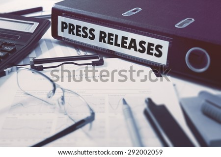 Press Releases - Office Folder on Background of Working Table with Stationery, Glasses, Reports. Business Concept on Blurred Background. Toned Image.