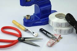 Press, scissors, thread cutter, size box on a white background. A set of instruments for sewing clothes. Various types of tools for sewing production.
