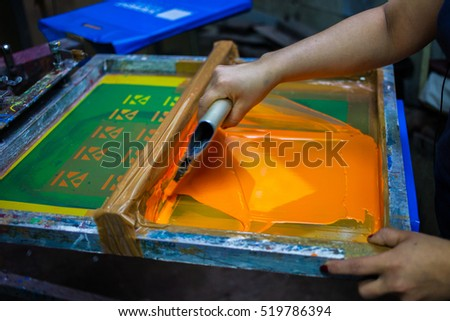 Press silk-screen printing by orange paint. Screen Print.
