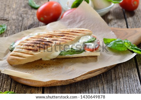 Pressed and toasted panini caprese with tomato, melted mozzarella and basil, served on sandwich paper on a wooden table Stok fotoğraf ©
