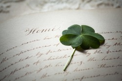 Pressed Four Leaf Clover and Antique Calligraphy Handwriting about Home