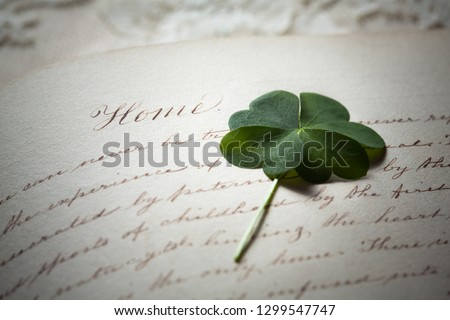 Pressed Four Leaf Clover and Antique Calligraphy Handwriting about Home #1299547747