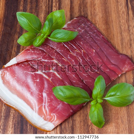 Pressed ham meat on wooden board with basil leafs