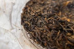 Pressed Pu-erh tea cake from Yunnan province, China. Beautiful fermented aged tea leaves. Macro close up. Sheng Puer - Chuan Cheng 2013.