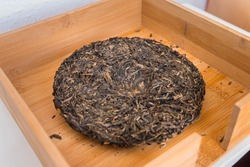 Pressed Pu-erh tea cake from Yunnan province, China. Beautiful fermented aged tea leaves (Sheng Puer). Chuan Cheng 2013.