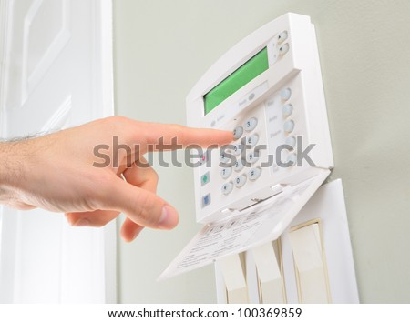 pressing the code on a house alarm - stock photo