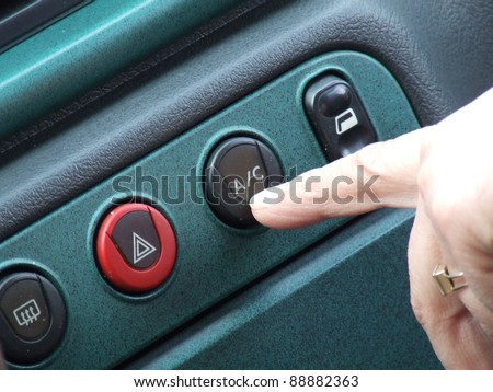 Pressing the index finger on the button on the air conditioner in the car