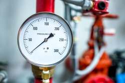 pressure gauge psi meter in pipe and valves of fire emergency system industry focus closeup middle red background