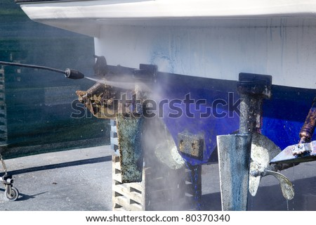 pressure washer cleaning boat hull barnacles anti-fouling and seaweed - stock photo