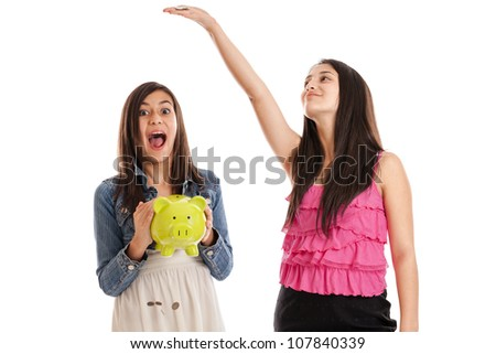 Preteen and teen sisters dropping money from a piggy bank isolated on white background