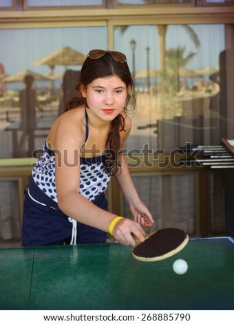 preteen beautiful girl play table tennis in the beach resort hotel recreation area