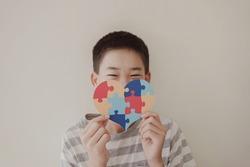 Preteen boy holding puzzle jigsaw heart shape,  child mental health concept, world autism awareness day, teen autism spectrum disorder awareness concept